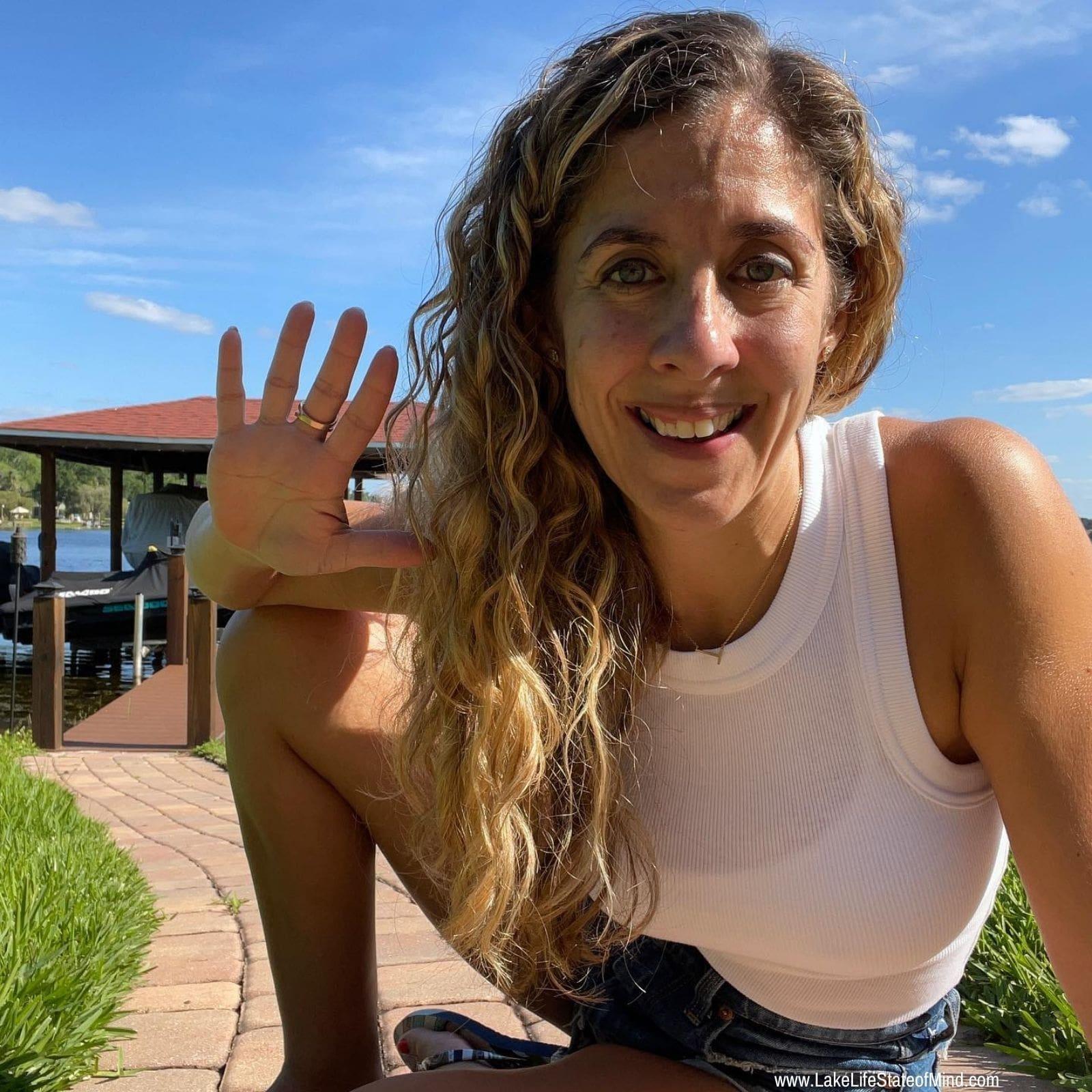 girl waving at the lake