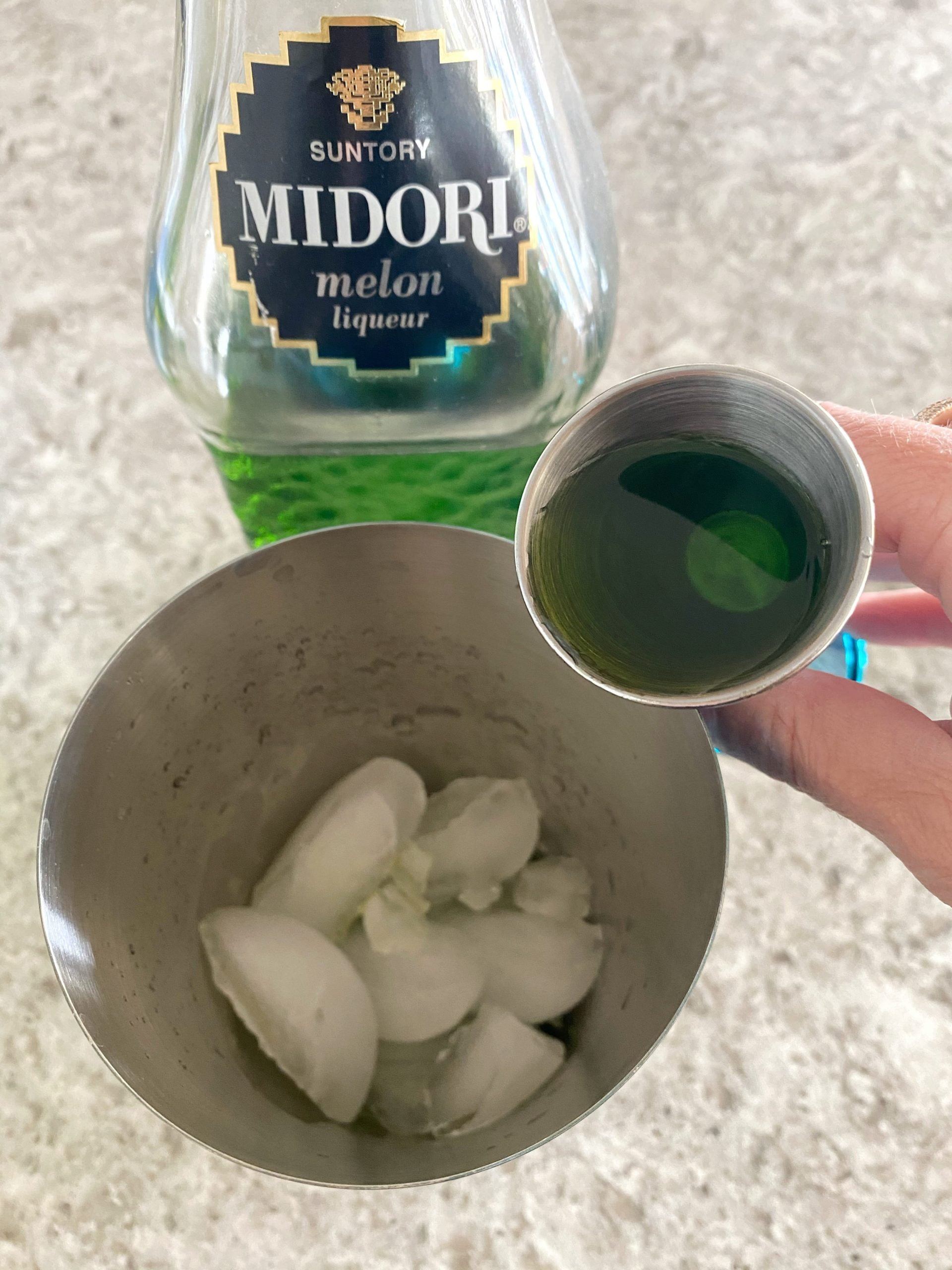 adding Midori to a cocktail shaker