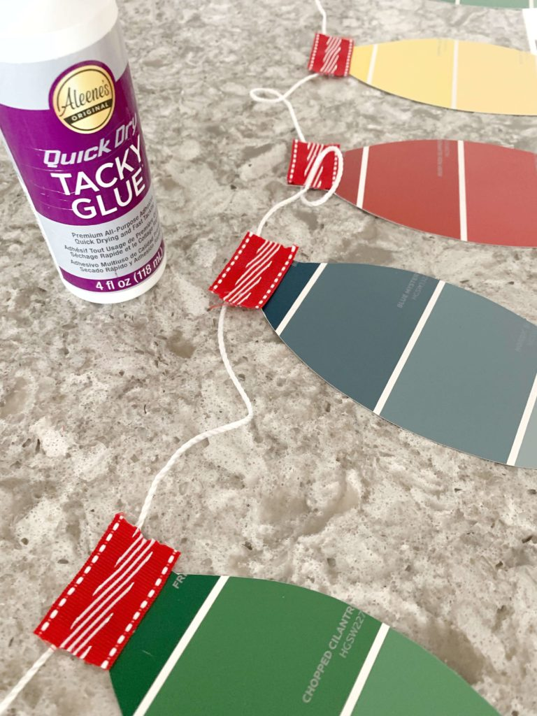 This DIY Christmas Lights Paint Chip Banner is the perfect easy Christmas craft to make with your kids this Christmas. This craft is not only simple but cheap to make! In ten short minutes, you'll have an adorable Christmas decoration to hang on your mantle or wall in your home. #banner #paintchips #easychristmascraft #lakelifestateofmind