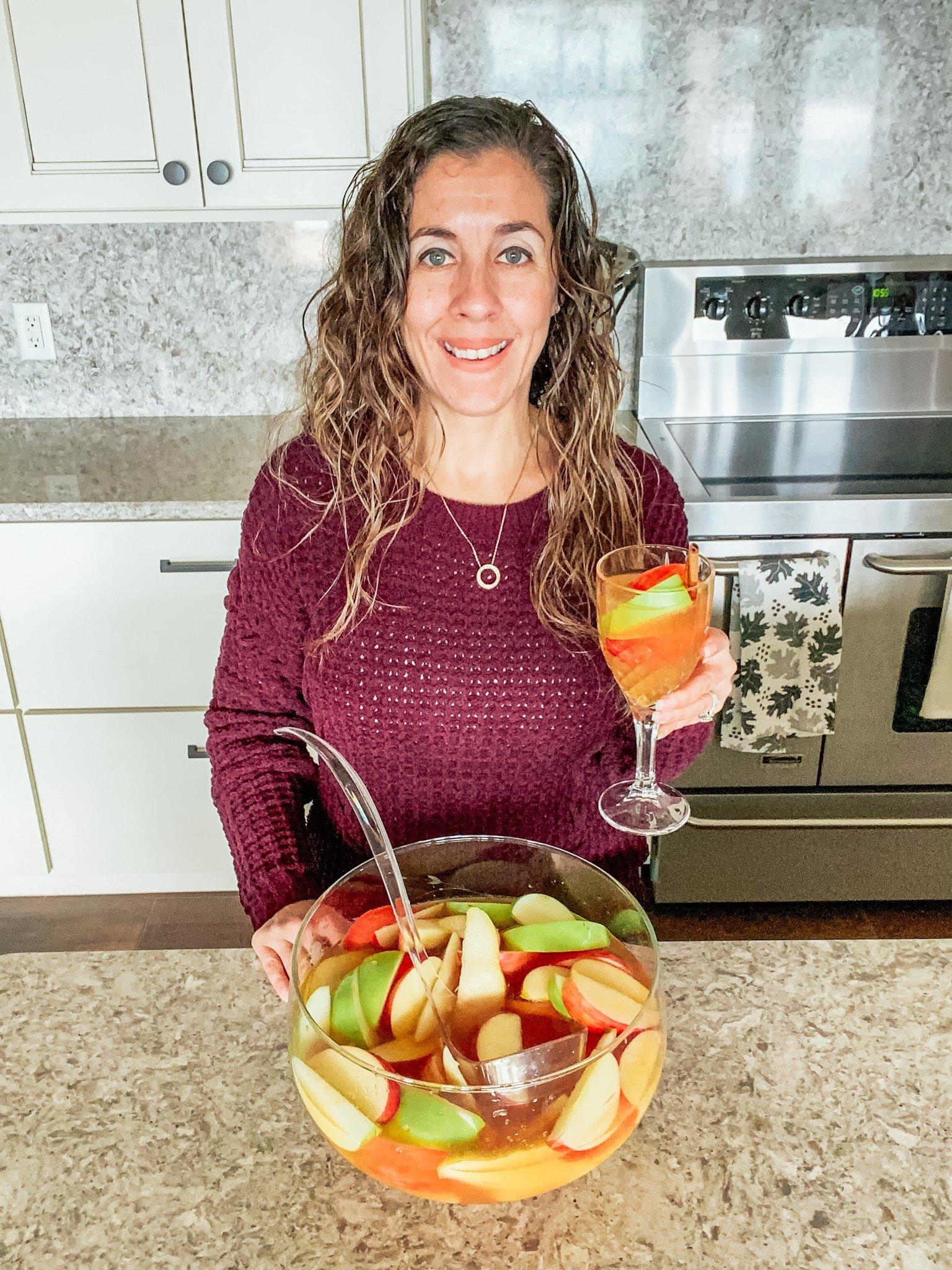 woman holding apple cider sangria