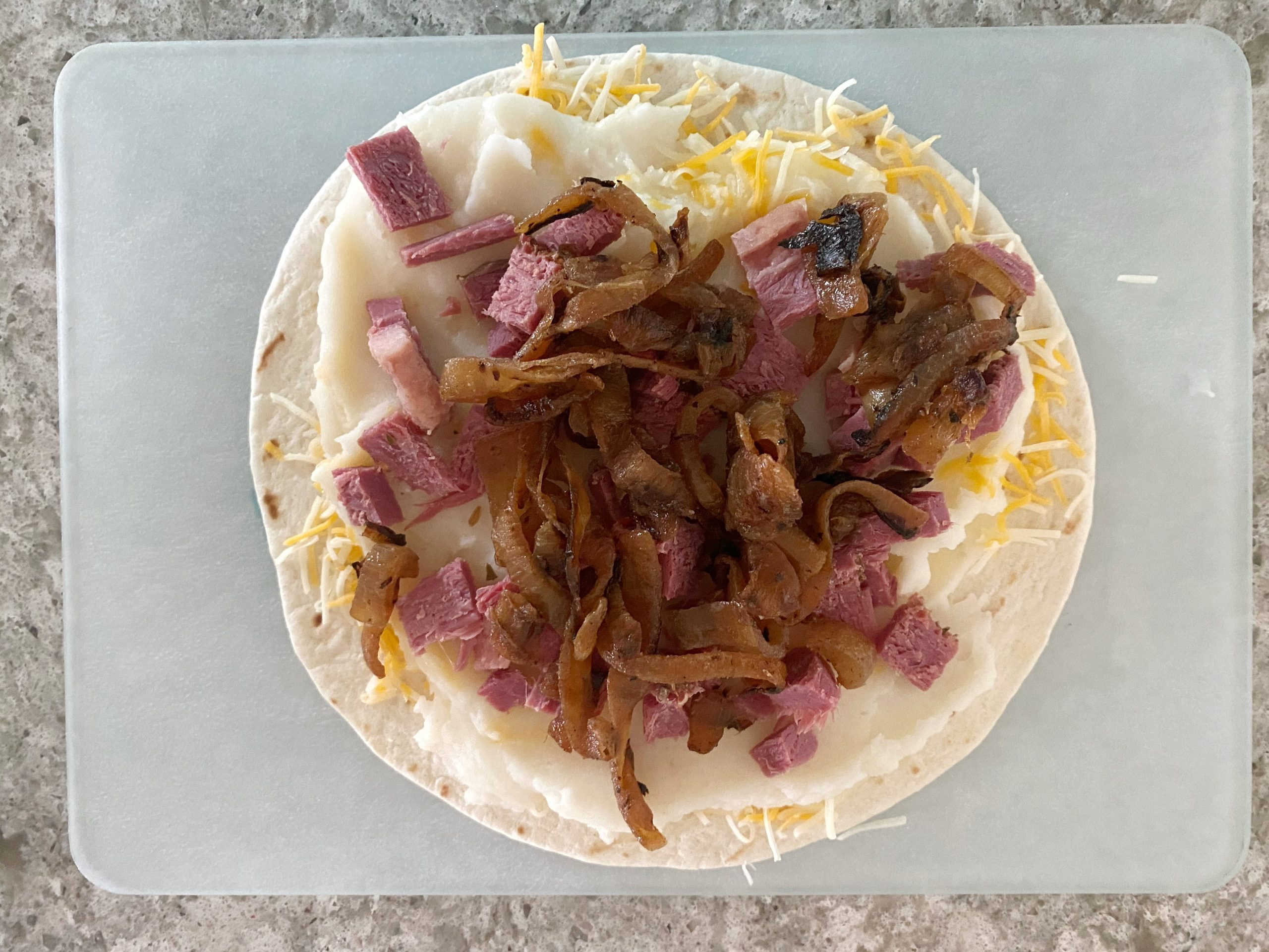 caramelized onion, corned beef, cheese and mashed potatoes on tortilla