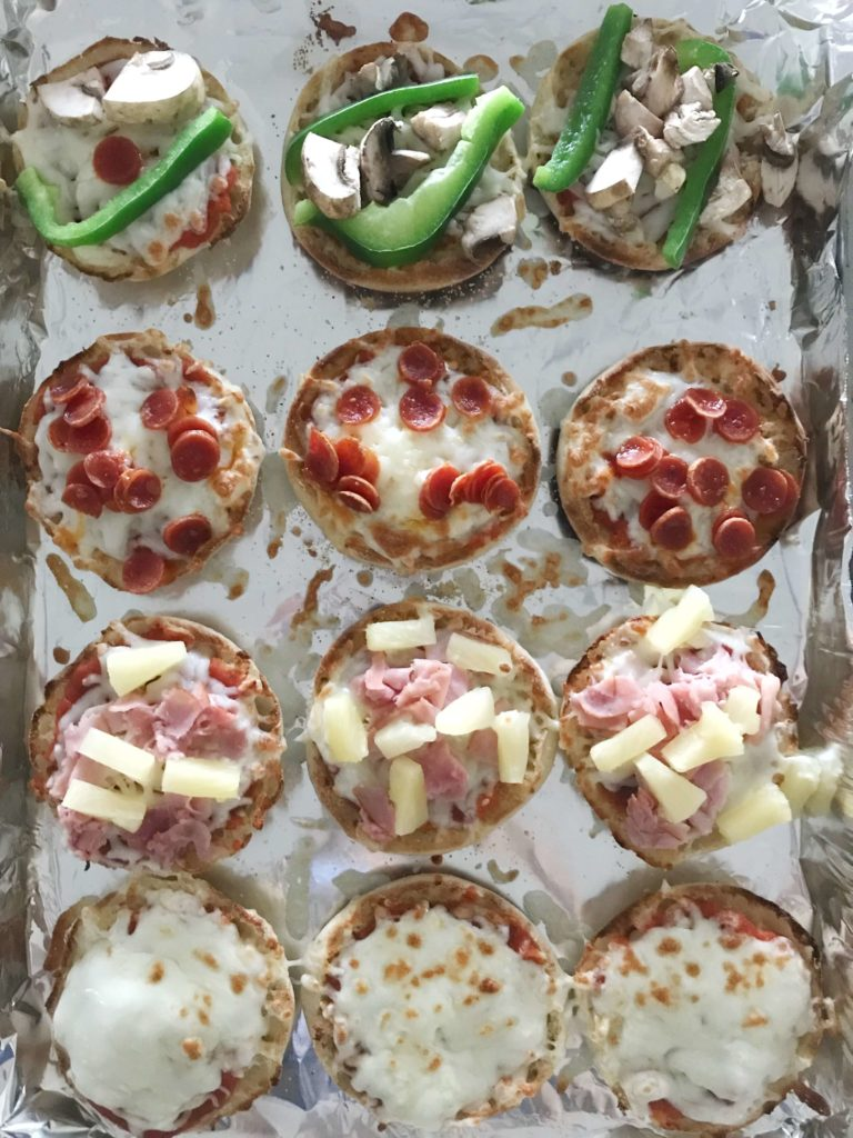 Looking for an easy dinner option that everyone in your family will go crazy for? Look no further than these English Muffin Pizzas that can be prepared and on the dinner table in less than 10 minutes. Dad likes pepperoni pizza. Mom likes the Hawaiian variety with ham and pineapple. The kids are picky and will only eat cheese pizza. No worries! These English Muffin Pizzas are customizable to meet everyone's pizza needs. #easyrecipes #weeknightdinner #cookingwithkids #pizza
