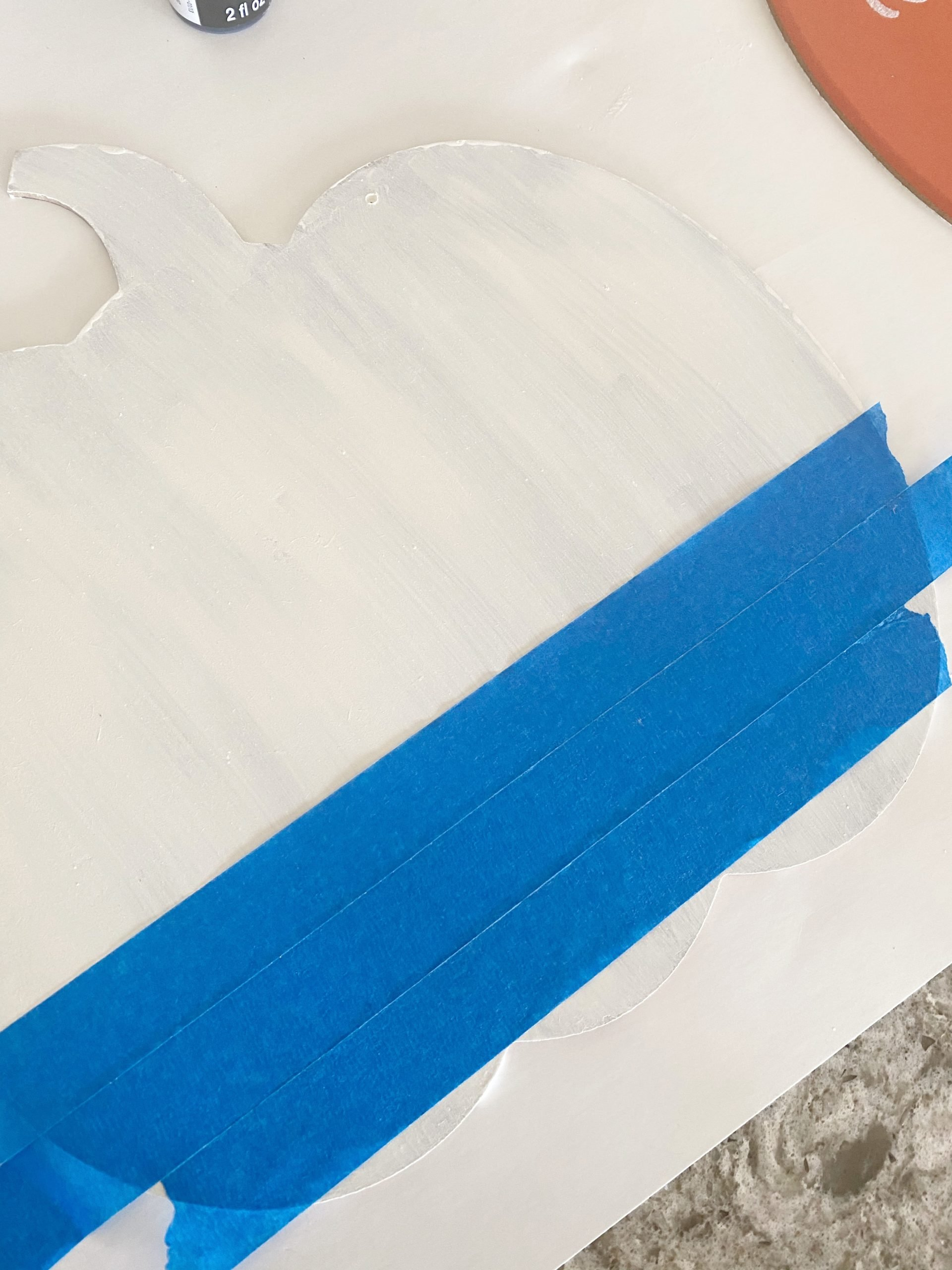 blue painter's tape on white pumpkin sign